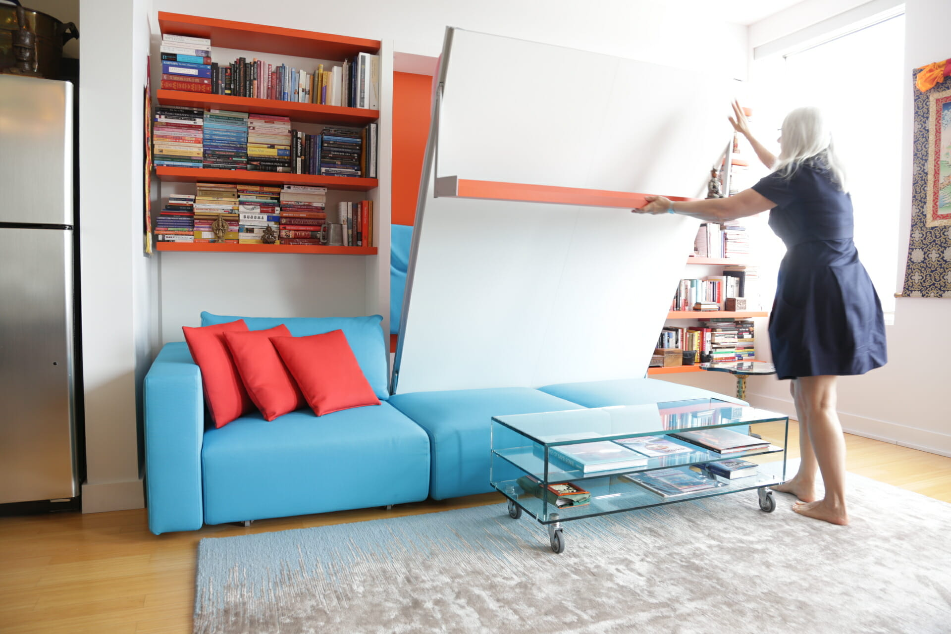 Van Duren demonstrates the ease of lowering the Swing, a queen-size wall bed with nine-foot sofa and sliding chaise. Here, it integrates with a shelving system, which continues the apartment's quirky motif of orange and blue.