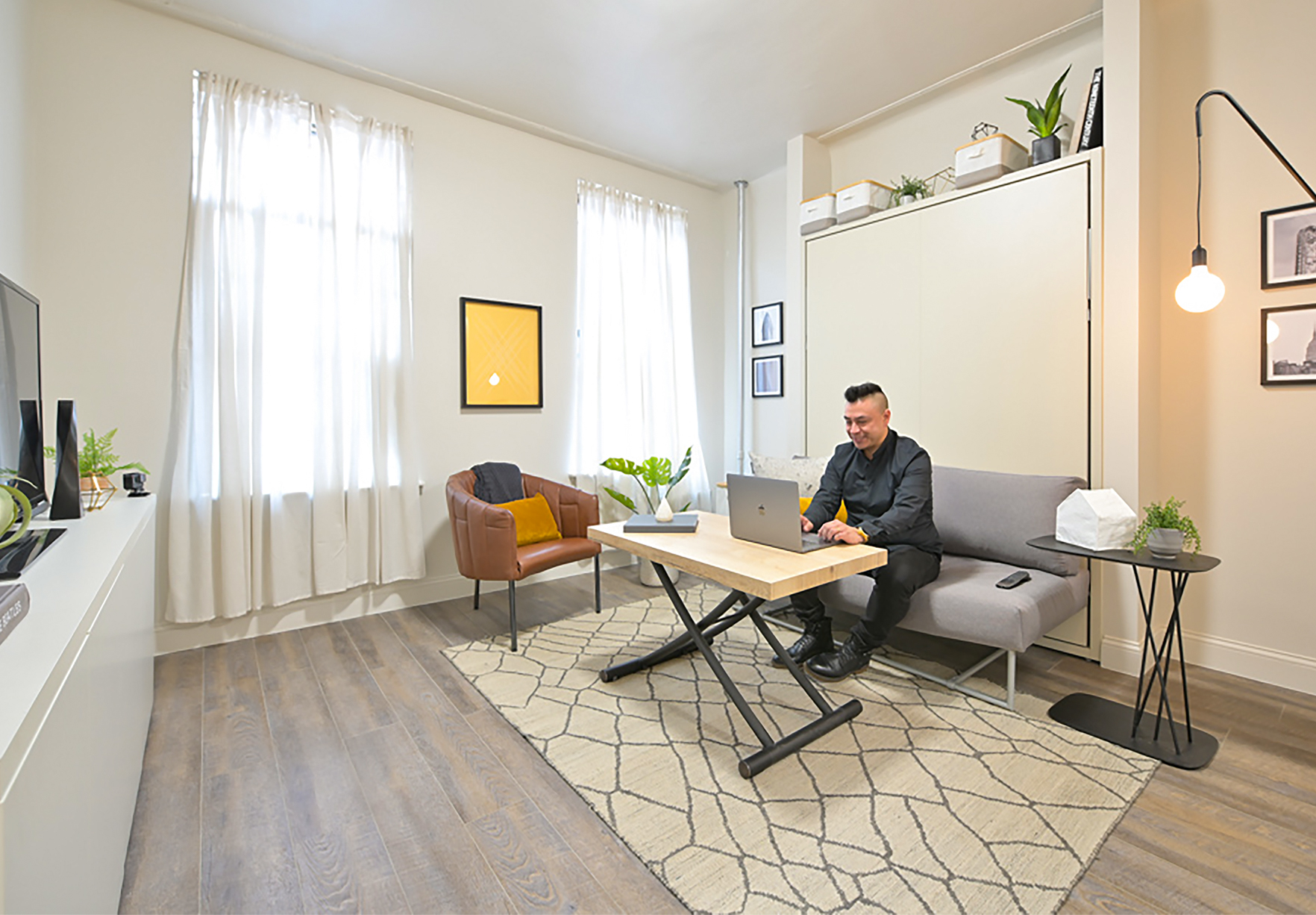 Using a multi-functional sofa wall bed and height-adjusting coffee table, this 300sqft NYC studio transforms from bedroom to living room to home office in seconds.